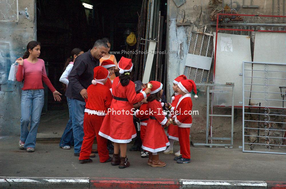 Children dressed up as Santa Claus in a parade in Wadi Nisnas, Haifa, Israel during the Holiday of holidays festival, celebrating Hanuka-Christmas-Ramadan festival in the Haifa Neighbourhood of Wadi Nisnas