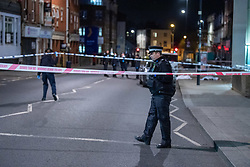 © Licensed to London News Pictures. 10/04/2021. London, UK. A police officer standing at a cordon after a 17-year-old boy was fatally stabbed in Sydenham. Police were called to Hazel Grove, junction with Sydenham Road, at 19:19BST on Saturday, 10 April after reports of a male lying injured on the ground. Officers attended with medics from the London Ambulance Service and the London Air Ambulance. They found a 17-year-old male who had been stabbed. Despite the best efforts of the emergency services, he was pronounced dead shortly after 20:00hrs. His next of kin have been informed. Photo credit: Peter Manning/LNP