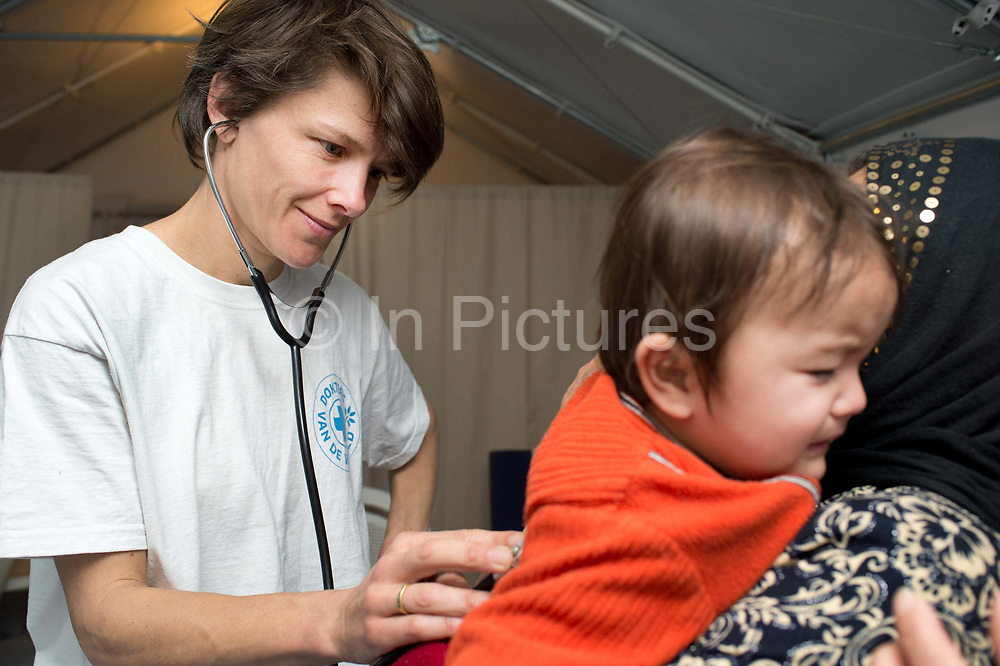 Greece with Doctors of the World (Medecins du monde). Chios Island, one of the places where refugees from Turkey land en route to Northern Europe. Souda camp. British doctor Dr Sophie Quinney examines baby Ashrafi from Afghanistan