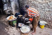 Trader cooking snacks in dark alleyway street in Zebid, Zabid, Yemen 1998 UNESCO World Heritage Site