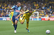 Wycombe Wanderers defender Michael Harriman (16) battles for possession  with Oxford United midfielder (on loan from Sheffield United) Ricky Holmes) (12) during the EFL Sky Bet League 1 match between Wycombe Wanderers and Oxford United at Adams Park, High Wycombe, England on 15 September 2018.
