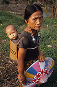 DAYAK, MALAYSIA. Sarawak, Borneo, South East Asia.Dayak, 'Kenyah', woman and child in papoose. Tropical rainforest and one of the world's richest, oldest eco-systems, flora and fauna, under threat from development, logging and deforestation. Home to indigenous Dayak native tribal peoples, farming by slash and burn cultivation, fishing and hunting wild boar. Home to the Penan, traditional nomadic hunter-gatherers, of whom only one thousand survive, eating roots, and hunting wild animals with blowpipes. Animists, Christians, they still practice traditional medicine from herbs and plants. Native people have mounted protests and blockades against logging concessions, many have been arrested and imprisoned.