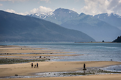 Beachcombers walk the beach at the Gustavus ferry dock during low tide. Gustavus is a tiny town in southeast Alaska located on the Icy Straight next to Glacier Bay National Park and Preserve. Pictured in the background is Excursion Ridge.