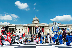 © Licensed to London News Pictures. 18/07/2021. LONDON, UK. Actors take part in a game of human chess at Chess Fest in Trafalgar Square.  The event celebrates the game of chess and visitors can learn the game, play chess or challenge a Grandmaster.  Also, to celebrate the 150th anniversary of Lewis Carroll's Alice Through the Looking Glass book which featured the game of the chess, 32 actors dressed as Alice Through the Looking Glass characters stand on a giant chessboard replaying a game based on the book.  Photo credit: Stephen Chung/LNP