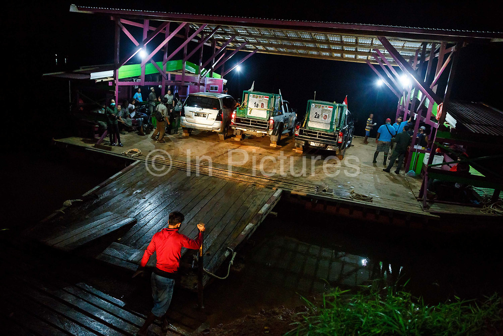 Pick-up trucks carying six orang-utans to be released into the wild are carried across a river by a ferry boat in Central Kalimantan, Borneo, Indonesia on 22nd May 2017. The animals are being taken by road and river from Nyaru Menteng Rehabilitation Centre, run by the Borneo Orangutan Survival Foundation, to a release site in Bukit Baka Bukit Raya National Park. Their health is checked by vets every two hours, and they are kept sedated for the whole journey.