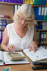 Woman using a calculator to check invoices,