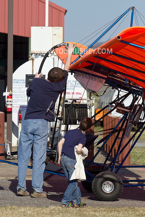 Middletown, New York - A pilot fuels his experimental aircraft as a young boy looks on at Randall Airport on  April 12, 2014. The MX II Sprint ultralight is powered by a four-cycle engine.