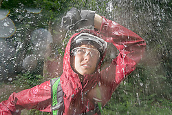 Mountainbiker standing in rain with hand over head, Kampenwand, Bavaria, Germany