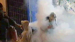 © Licensed to London News Pictures. 18/08/2011.London, UK. A still from CCTV showing a man being sprayed with a fire extinguisher after pleading with a group looters during the London Riots not to damage a shop front. The gang  used a fire extinguisher to smash the Carphone Warehouse shop window in Clapham Junction before looting the store. Police are trying to locate the victim Photo credit : London News Pictures