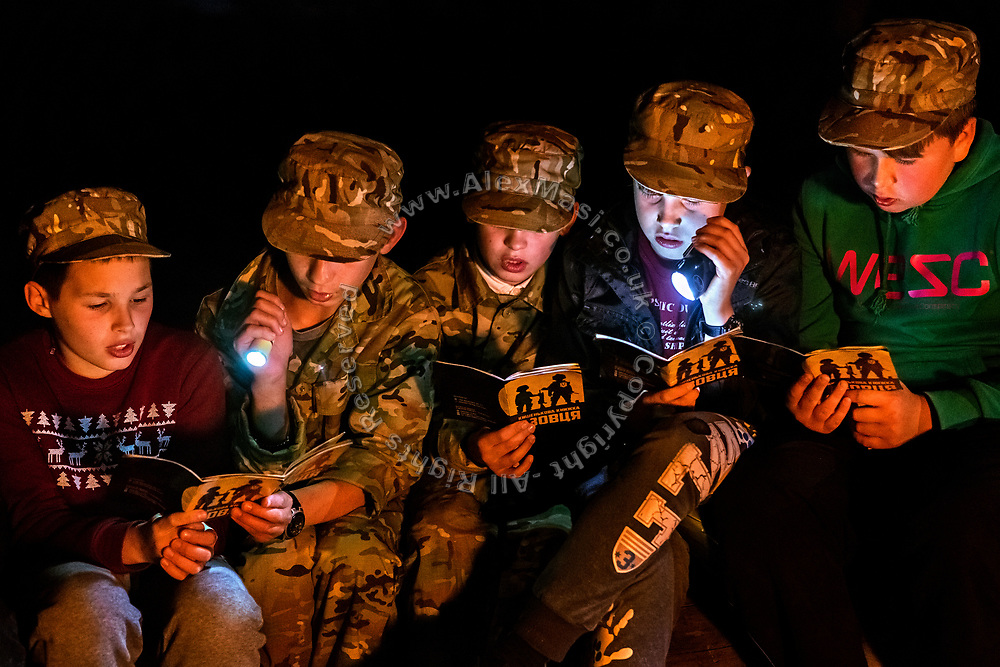 Boys participating to the ultra-nationalistic Azovets children's camp are reading and singing songs written on their induction book, while sitting together around the evening bonfire, on the banks of the Dnieper river in Kiev, Ukraine's capital.