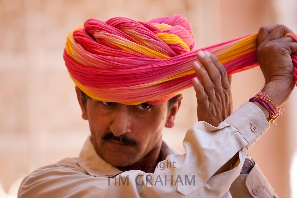 Hindu ceremonial guard putting on Rajasthani turban at Mehrangarh Fort at Jodhpur in Rajasthan, Northern India