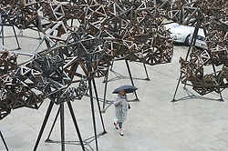© London News Pictures. 29/05/15. London, UK. A member of the public walks under Conrad Shawcross's new installation 'The Dappled Light of the Sun' in the Royal Academy Courtyard, Central London. Photo credit: Laura Lean/LNP
