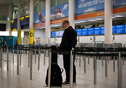 © Licensed to London News Pictures. 23/09/2019. Gatwick, UK. A passenger waits near Thomas Cook check-in desks at Gatwick Airport after the travel firm collapsed overnight. The 178 year old travel operator has gone in to liquidation after rescue talks failed overnight. This will trigger the largest peacetime repatriation as more than 150,000 British holidaymakers will need to be brought home. Photo credit: Peter Macdiarmid/LNP