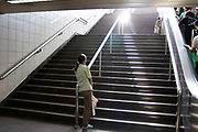 Woman waits for her child at the bottom of the stairs into People's Square Metro station. At this time of day a shaft of light penetrates below ground.