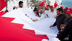 © under license to London News Pictures. 21/02/2011. A man places a rose on the Bahraini Flag as a symbol of peace as protesters march around Pearl Roundabout in Manama, Bahrain where thousands of people have gathered to protest for government reforms. Photo credit should read Michael Graae/London News Pictures