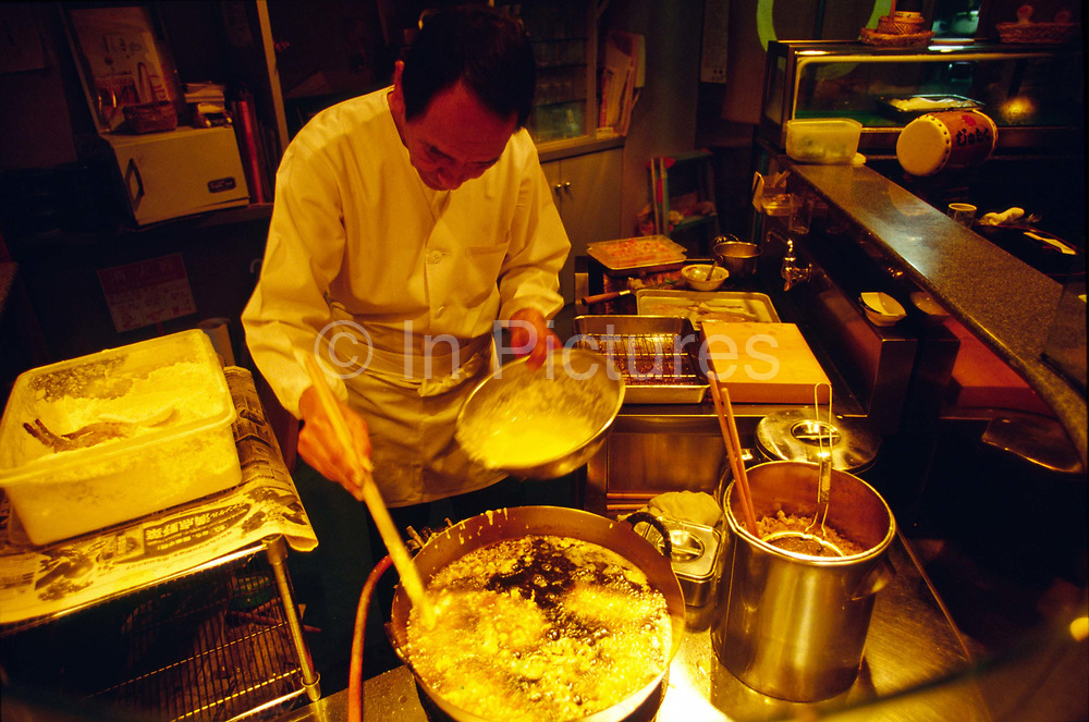 A tempura chef fries pieces of fish in oil in a small restaurant in Hakone, Japan.<br /> Although tempura is internationally famous and synonymous with Japanese cooking, it was introduced to Japan in the mid-sixteenth century by early Portuguese and Spanish missionaries and traders