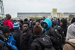 October 24, 2016 - Calais, France - Migrants stand in a line to register themselves in near the Calais Jungle. After registration, the migrants are distributed on buses. The refugee camp on the coast to the English Channel is to be cleared today. The approximately 8,000 refugees are distributed after the registration by busses to various reception centers in France. (Credit Image: © Markus Heine/NurPhoto via ZUMA Press)