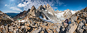 """Paso Quadrado affords a spectacular panorama south to Lago Quadrado, the North Fitz Roy Glacier, and peaks including Guillaumet, Mermoz, Fitz Roy, Cerro Torre, and Aguja Pollone (left to right), near El Chalten, Argentina, Patagonia, South America. We hiked scenic Rio Electrico Valley to Refugio Piedra del Fraile (""""Stone of the Friar"""", 14.5 km round trip) to stay overnight in dorms. A path from the refuge ascends very steeply to Paso Quadrado (gaining 1340 m vertically in 8.4 km round trip). The last kilometer climbs up steep snow which could require crampons if icy (but was passable in soft snow using our trailrunning shoes). Views keep improving as you ascend. Monte Fitz Roy is also known as Cerro Chaltén, Cerro Fitz Roy, or Mount Fitz Roy (3405 m or 11,171 ft elevation). The first Europeans recorded as seeing Mount Fitz Roy were the Spanish explorer Antonio de Viedma and his companions, who in 1783 reached the shores of Viedma Lake. In 1877, Argentine explorer Francisco Moreno saw the mountain and named it Fitz Roy in honour of Robert FitzRoy who, as captain of HMS Beagle, had travelled up the Santa Cruz River in 1834 and charted large parts of the Patagonian coast. Mt Fitz Roy was first climbed in 1952. Cerro is a Spanish word meaning hill, while Chaltén comes from a Tehuelche word meaning """"smoking mountain"""", due to clouds that usually form around the peak. This image was stitched from multiple overlapping photos."""