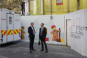 Two businessmen hold a conversation in front of a construction hoarding for a new Lego store in Leicester Square, central London.