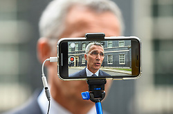 © Licensed to London News Pictures. 15/10/2019. LONDON, UK.  Jens Stoltenberg, NATO Secretary General, is seen on a smartphone giving a press interview outside Number 10 Downing Street, after meeting Boris Johnson, Prime Minister, for talks.  Photo credit: Stephen Chung/LNP