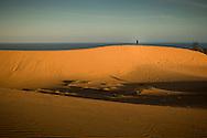 Distant figure stands on the massive sand dunes of Mui Ne, Binh Thuan Province, Vietnam, Southeast Asia