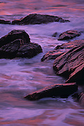 USA, Newport, RI - Sunrise reflects on the sea and wet, rocky shore of Sachuest point.