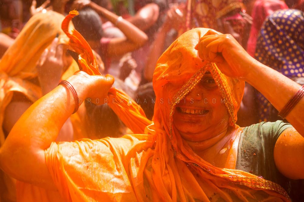 A woman hits the photographer with wet clothes at the Huranga festival, Dauji temple, Baldeo, India. Photo © robertvansluis.com