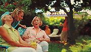 Three women sit together and talk while spending the day in a botanical garden