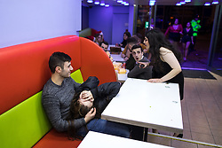 """© Licensed to London News Pictures . 24/12/2016 . Manchester , UK . A man cradles a woman in his lap inside Funky Chicken takeaway . Revellers out in Manchester City Centre overnight during 2016's second """" Mad Friday """" , named for historically being one of the busiest nights of the year for the emergency services in the UK . Photo credit : Joel Goodman/LNP"""