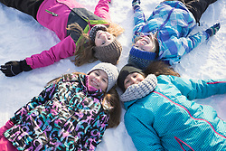 Portrait of girls lying on snow