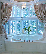 Window-lined restroom with soaker tub.