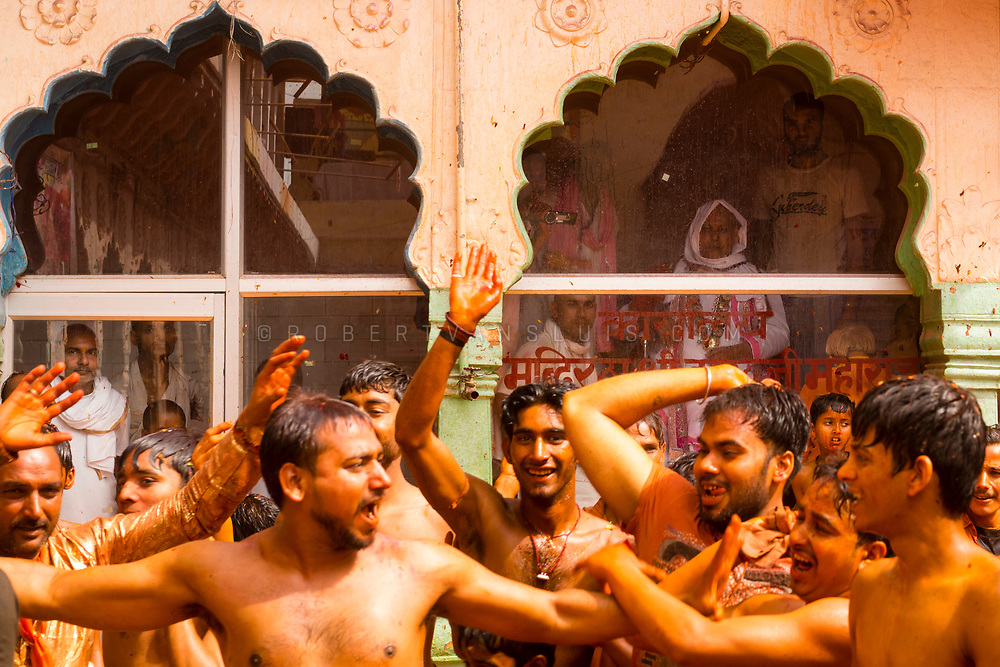 A group of men hit each other with wet clothes while the temple guru watches from behind glass at the Huranga festival, Dauji temple, Baldeo, India. Photo © robertvansluis.com