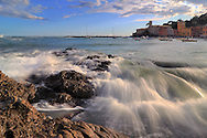 Reefs and crashing waves bathed in the warm sunset light at Baia del Silenzio (Silence Bay), one of the two bays encircling the small town of Sestri Levante in Liguria, Italy.