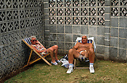 Beneath an ugly breeze block concrete wall, a couple are enjoying their holiday in the English seaside town of Paignton, Devon. Sitting in striped deckchairs they are both curiously touching their own genital areas between their legs, perhaps both scratching an itch. The lady in sunglasses wearing a floral dress on the left looks guilty while her topless male partner appears more amused by the interruption. In this depressing corner of Paignton, also called the English Riviera, the grey construction behind them is a grim reminder of what it is often like to holiday in one's own home country where few exotic luxuries are found. Such squalor is unfortunately common around the UK and a reason why people take their vacations abroad. Even the grass below them is bare with weeds growing and soil at the foot of the wall.