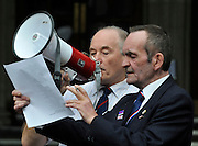 CENTRAL LONDON. BNP supporters sing The National Anthem using a songsheet. Nick Griffin leader of The British National Party outside the Royal Courts of Justice today after his case was adjourned.. 07 SEPT 2010. STEPHEN SIMPSON ..