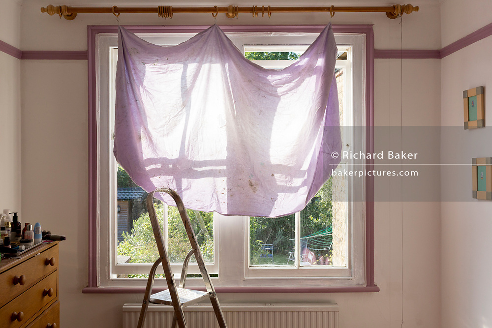 A temporary curtain that shades strong morning sunlight, hangs from a rail across a bedroom window during home repairs and the painting of a sash window in a period house in south London, on 25th May 2020, in London, England.