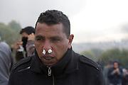 Manifestant anonym au cimetiere Jallez, qui souffre du gaz lacrymogene tire par la police. l'hommage du peuple Tunisien a Chokri Belaid fut perturbe par incidents entre jeunes casseurs et la police anti-emeutes. Des voitures sont brulees.