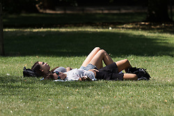 © Licensed to London News Pictures. 12/08/2016. LONDON, UK.  Two women sunbathe during the hot and sunny weather today in St James's Park in London.  Photo credit: Vickie Flores/LNP