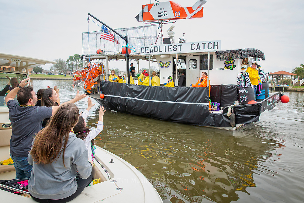 Geoff Trinehaud, left, The Krewe of Bilge Mardi Gras boat parade sails through the Eden Isles waterways on the northshore of Lake Pontchartrain in Slidell, La.  Founded in 1978 the Krewe has continuously cruised for over 40-years.