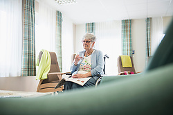 Senior woman in a wheelchair holding a glass of water