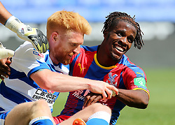 Crystal Palaces Wilfried Zaha and Reading's Paul McShane share a joke after a tackle during the pre-season friendly match at the Madejski Stadium, Reading.
