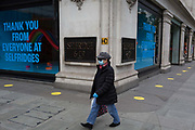 With the UKs Coronavirus pandemic lockdown easing with preparations going ahead for the opening of more public transport and services plus shops, another 151 have died from Covid-19 bringing the total in the last 24hrs to 41,279. A wider range of retailers are due to re-open their doors for non-essential purchases next Monday 15th June and  a shopper walks past Selfridges department store on Oxford Street whose windows thank NHS staff and key workers during the pandemic. Yellow stickers are also on the ground directing shoppers where to queue, on 11th June 2020, in London, England.