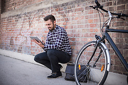 Young man using digital tablet and sitting against brick wall, Munich, Bavaria, Germany