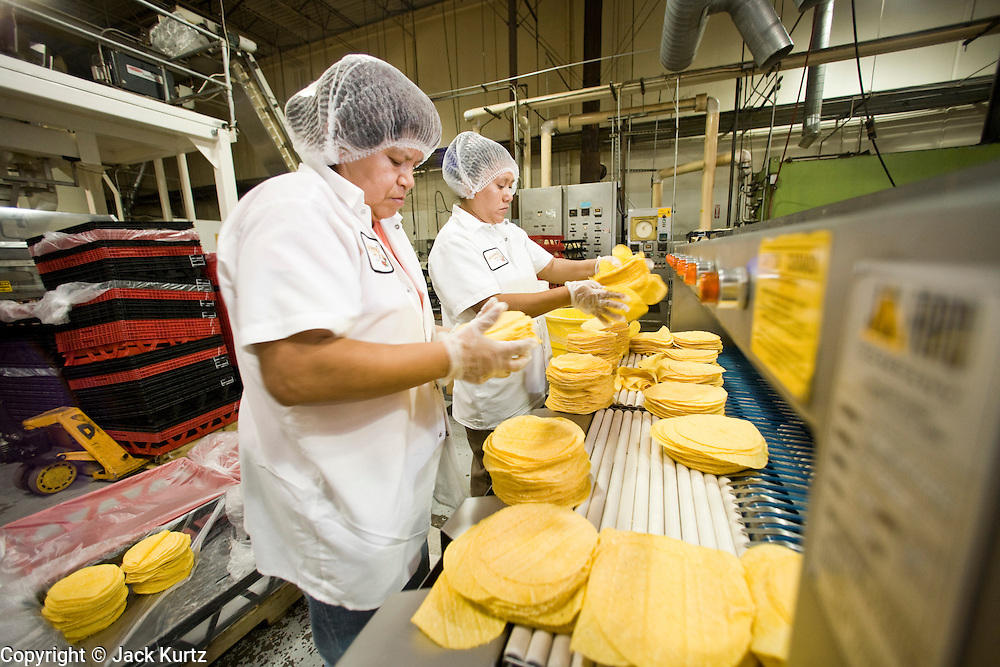 05 MAY 2008 -- PHOENIX, AZ: MARIA GONZALEZ and ELIZABETH LOPEZ pack corn tortillas on the production line at La Canasta in Phoenix. La Canasta uses 20,000 - 25,000 pounds of corn daily to make almost two million tortillas. Josie Ippolito, President of La Canasta, said the price of the corn she buys has shot up more than 50 percent since November, 2007 and is expected to double by the end of this year. This in addition to the 200 percent increase in the price of wheat flour she uses in other products at La Canasta.   Photo by Jack Kurtz