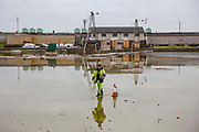 A man dressed in hi-vis working for Sweeptech supervises the cleaning out of rubbish and silt from the bottom of Hove Lagoon, Kingsway,  Hove, East Sussex, United Kingdom.