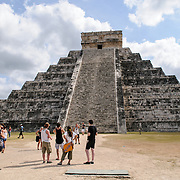 A group of tourists visiting the Temple of Kukulkan (El Castillo) at Chichen Itza Archeological Zone, ruins of a major Maya civilization city in the heart of Mexico's Yucatan Peninsula.