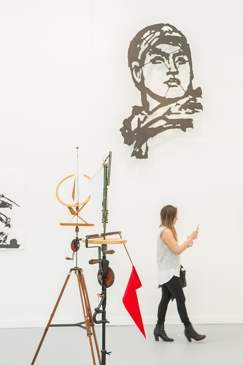New York, NY - 6 May 2016. Frieze New York art fair. A visitor takes in the exhibits in the Marian Goodman Gallery, which has outlets in New York, London and Paris.