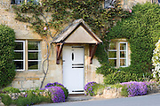 Typical cottage doorway and porch with aubretia shrubs in Stanton village, The Cotswolds, Gloucestershire, England, United Kingdom