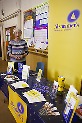 Age concern carers week; lady standing at Alzheimers stall displaying leaflets,
