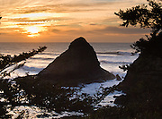 "Surf pounds a sea stack seen offshore from Heceta Head at sunset, on the Oregon coast, USA. To get here, take Highway 101 south of Yachats to ""Heceta Head Lighthouse State Scenic Viewpoint"" and walk the 0.5-mile trail towards the lighthouse."
